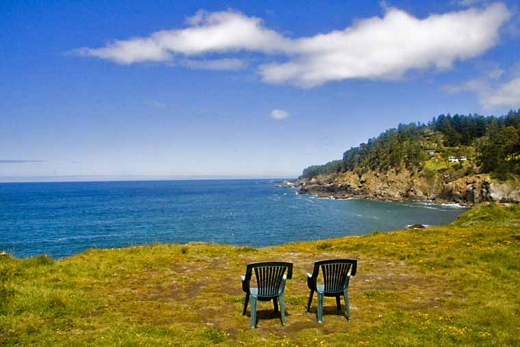 Two chairs of the bluff with ocean in background